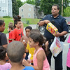 Fitchburg Police Officer Jose Figueroa hands out popsicles to local children after they listened to a story about the Fitchburg Reading Trolley on Wednesday evening at Green Acres in Fitchburg. SENTINEL & ENTERPRISE / Ashley Green