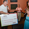 Rick Rossi, of ACE Animal Care & Education, presents 8-year-old Olivia Lambert a check for five hundred dollars at Primetime Pub in Lunenburg on Friday night. Olivia is waiting on a diagnosis of her type of autism and has been raising money to get herself a service dog. SENTINEL & ENTERPRISE / Ashley Green