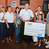 Rick Rossi, of ACE Animal Care & Education, presents 8-year-old Olivia Lambert a check for five hundred dollars at Primetime Pub in Lunenburg on Friday night. Olivia is waiting on a diagnosis of her type of autism and has been raising money to get herself a service dog. Pictured are Jess Demeo, Kim Hartwell, Cindy Correll, Meg Johnson, Rick Rossi, Olivia Lambert, and Olivia's parents Debra and Bruce Lambert. SENTINEL & ENTERPRISE / Ashley Green