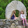 Bella Arpano, 5, and her friend Addison, 4 on right, hang out behind the Ashburnham Town Hall on a memorial commemorating the early grist mills in the town during the warm but windy weather on Tuesday afternoon. SENTINEL & ENTERPRISE/JOHN LOVE