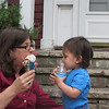 Baby has an empty water bottle; Mommy has an ice cream cone