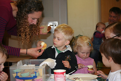 Jo helping Joshua decorate a cupcake. James looking at Eva decorating another cupcake. He still hasn't left the cupcake table!