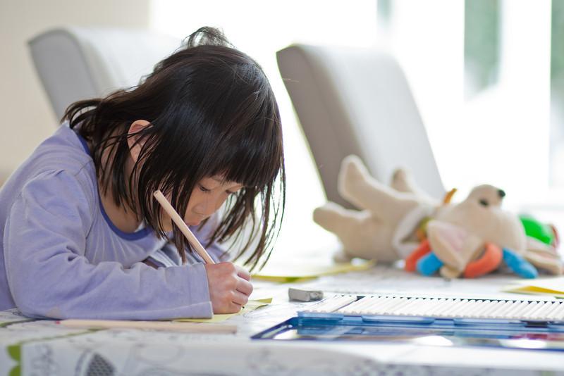 Caroline kleurt een zelfgemaakt stripboekje. Op de achtergrond haar onafscheidelijke knuffel Wofje.