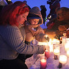 Leona Phaneuf and her grandson Adrian Espinal-Phaneuf, 2, place their candles at the memorial during the vigil for Jeremiah Oliver, 5, who has been missing since Sept. 14, 2013. SENTINEL & ENTERPROSE/JOHN LOVE