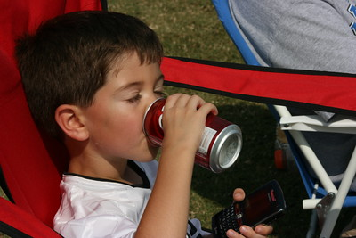 Kevin thinking he is cool at the soccer game by drinking Daddy's Dr.Pepper and playing with the Blackberry.