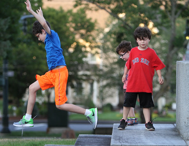 Brothers Declan McDonnell, 11, left, Shamus Desjardins, 7, right, and Callan Desjardins, 3, of Arlington, play by the Revolutionary War Monument on Chelmsford Common while their parents play Pokemon Go. Their father works in Chelmsford and like the Chelmsford Common Pokemon Go spot, with room for kids to run around. (SUN/Julia Malakie)