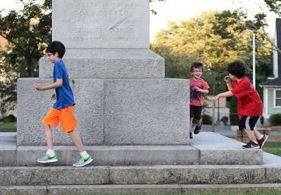 Brothers Declan McDonnell, 11, Shamus Desjardins, 7, and Callan Desjardins, 3, of Arlington, play by the Revolutionary War Monument on Chelmsford Common while their parents play Pokemon Go. Their father works in Chelmsford and like the Chelmsford Common Pokemon Go spot, with room for kids to run around. (SUN/Julia Malakie)