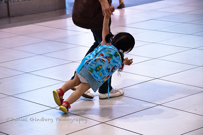 A mother holding her daughter's hand inadvertently drags her in the train station in Hamamatsu, Japan.