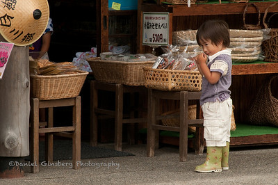 A young boy in front of a store gazes at something, in Shirakawa, Japan.