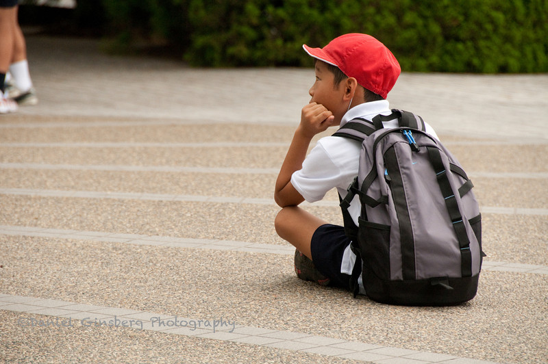A schoolboy sits alone while his classmates visit the Children's Peace Monument in Hiroshima.
