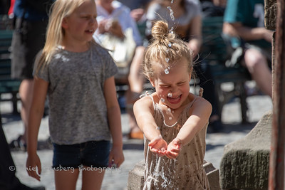 Young girl wetting hands in fountain in Stockholm, Sweden.