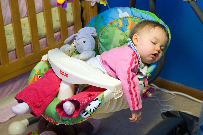 "Kyrie asleep in the swing with her ""bunbun."""
