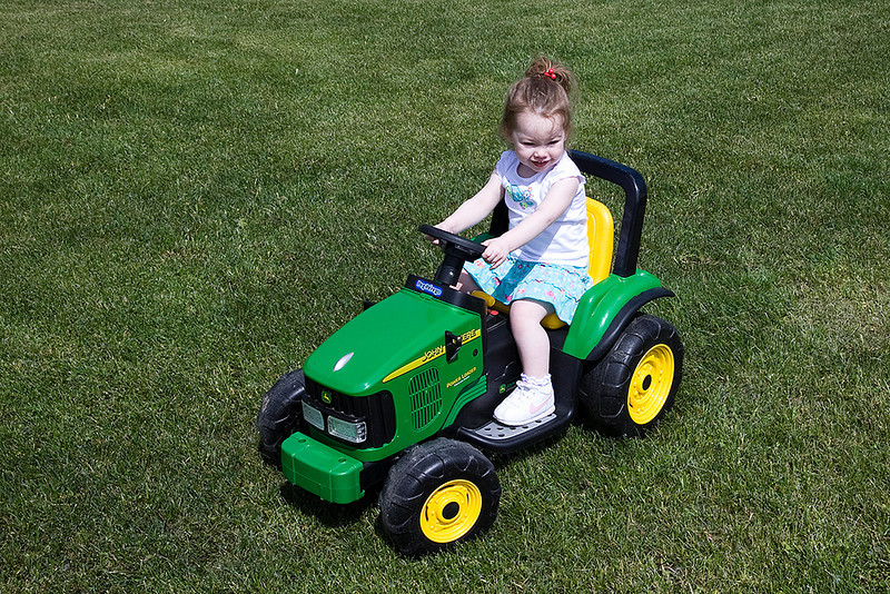 Riding her tractor.