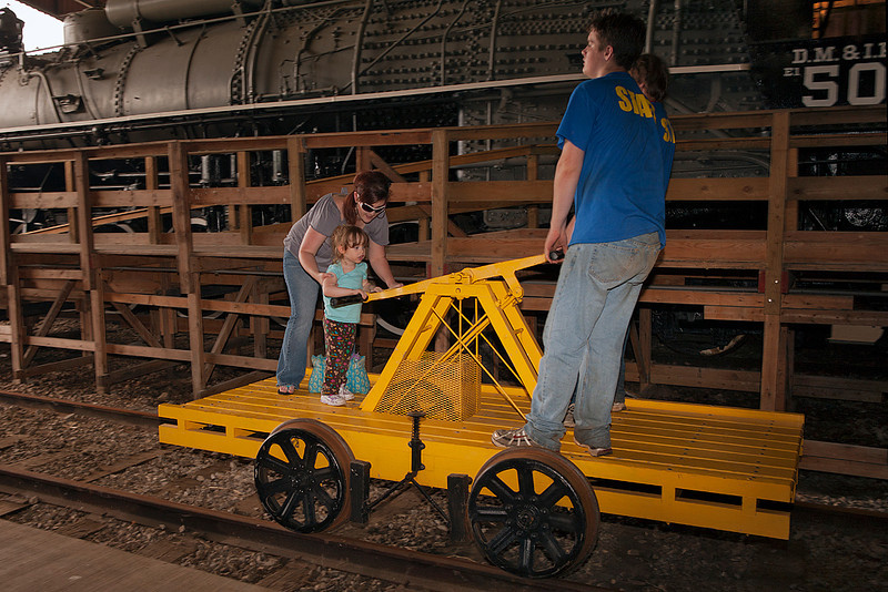 Mommy and Kyrie ride and help pump the handcar