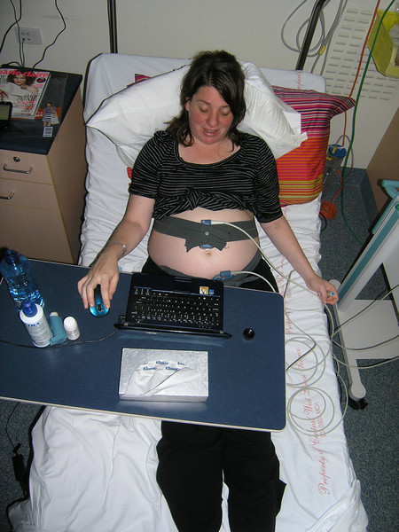 Holly hooked up to the monitor, being observed for high blood pressure.  And using Facebook.
