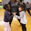 Afternoon dance party for pre-schoolers at the Greater Lowell YMCA. Amanda Wanjiku, 4, left, and Vivianna Lim, 4, dance with teacher Jennifer Khuy. All are from Lowell. (SUN/Julia Malakie)