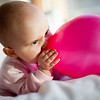 Baby blowing a baloon