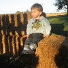 How about sitting on the straw bails?  This one is pretty good.  He's looking into the sunset.  Notice his socks match his sweatshirt... so cute!
