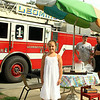 Olivia Lambert stand at her Lemonade stand with Leominster Ff's in the background talking to her father Bruce.