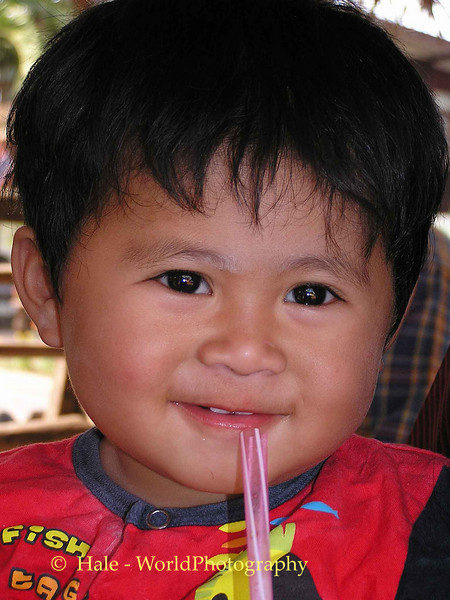 Baby Kwan Playing with a Straw, Thasang Village, Isaan Thailand