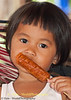 Fheng Enjoying Her Deep Fried Hot Dog Dipped In Chili Sauce