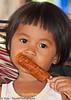 Fheng Enjoying Her Deep Fried Hot Dog Dipped In Chili Sauce