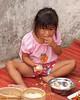 Rocket Vendor's Daughter Eating Her Breakfast in Baan That, Thailand