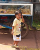 Young Lao Loum Girl Walking Past A Donut Cart