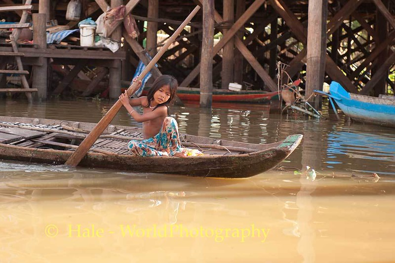 Young Cambodian Girl Poling Boat Down Flooded Street