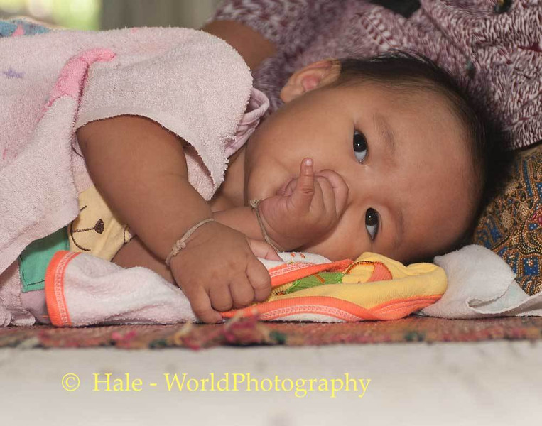 A Tired Baby Rests While Her Grandmother Prays