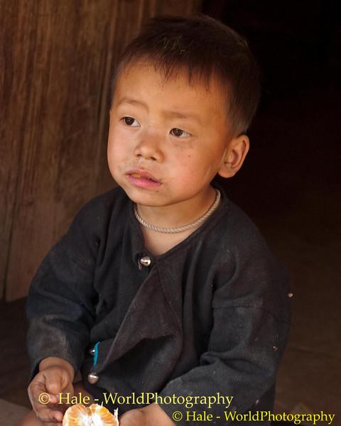 Lanten Boy Eating An Orange In Front of His Home In Ban Nam Dee, Laos