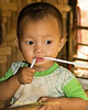 Refugee Baby Chewing On a Straw