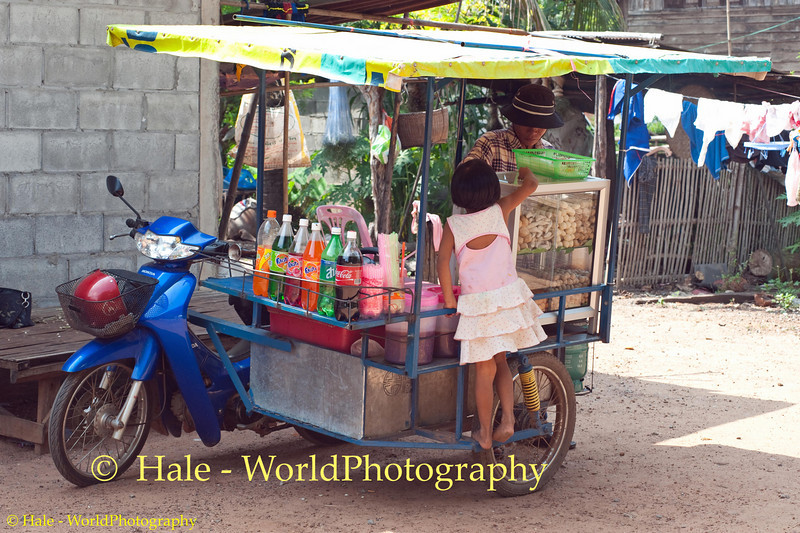 Lao Loum Child Buying A Snack Off of a Food Cart