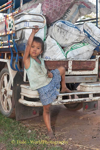 Coyly Posing In Front Of Her Uncle's Cart Filled With Bags of Charcoal