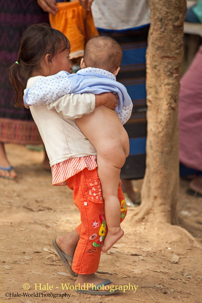 Young Hmong Girl Carries Her Baby Brother at New Year's Festival in Luang Prabang, Lao People's Democratic Republic