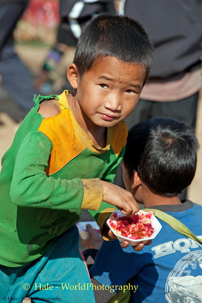 Akha Boy Enjoying A Shaved Ice Treat At the Xieng Kok Market, Laos