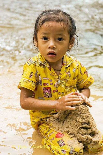Girl Making Mud Castle in River - Phnom <br /> Kulen, Cambodia