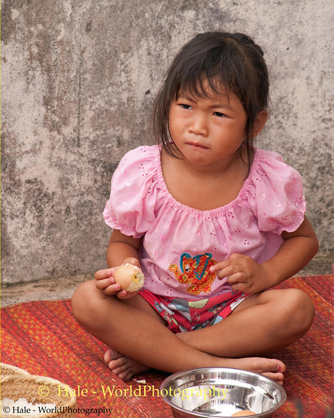 Rocket Vendor's Daughter Eating Her Breakfast in Baan That, Thailand