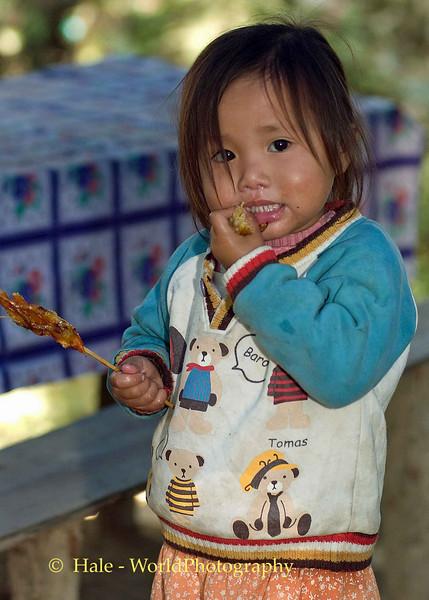 Hmong Child Eating at New Year Festival - Luang Prabang, Laos