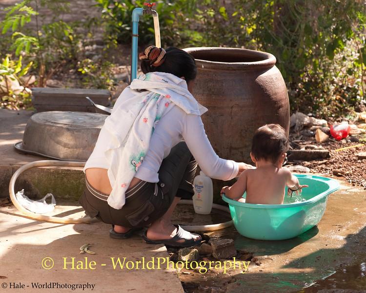 Grandmother Duangchan Gives Peelawat His Bath In Tahsang Village