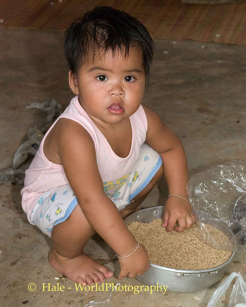 Lao Loum Child Playing with Food, Tahsang Village Thailand
