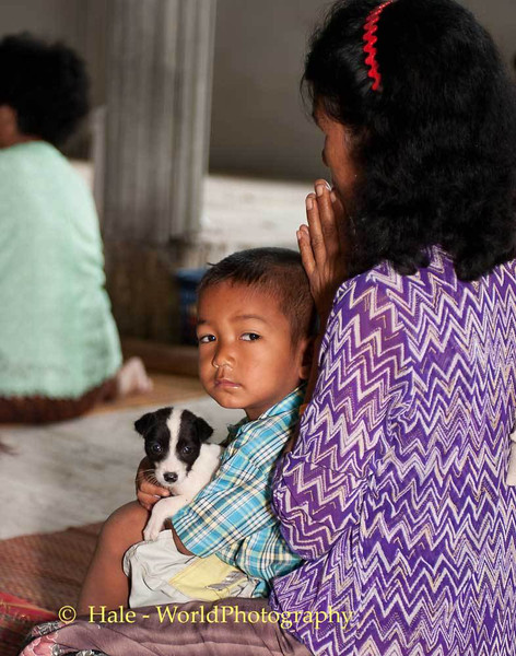 A Young Boy and His Puppy In the Comfort of His Mother's Lap During Merit Making Ritual