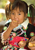 Hmong Child Eating Manadrin Orange at New Year Festival in Luang Prabang, Laos