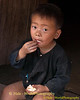 Lanten Boy Eating An Orange In Front of His Home In Ban Nam Dee, Laos