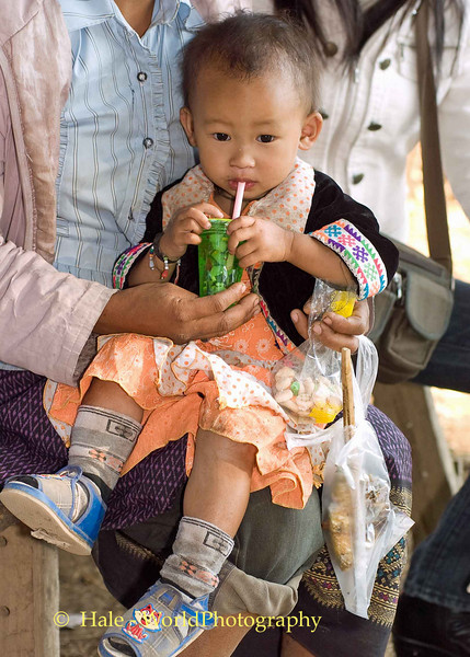 Hmong Toddler Enjoying a Drink at New Year Festival in Luang Prabang, Laos