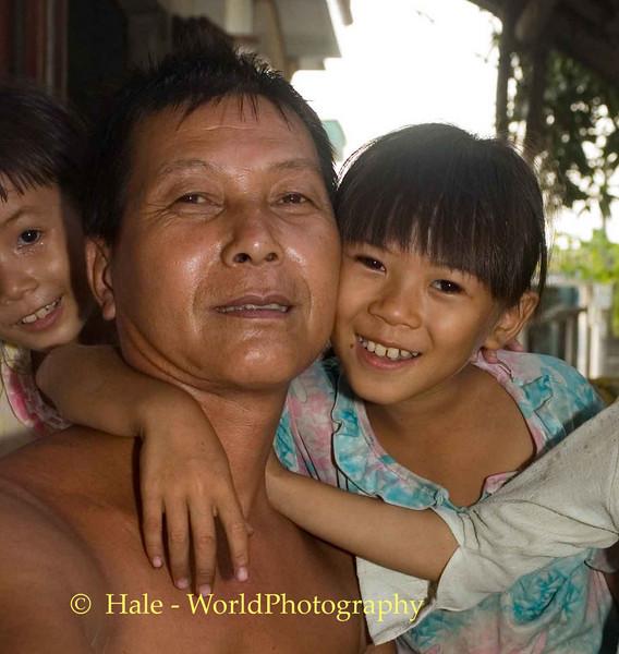 Young Daughter Hugging her Father, Quan Lan Island Vietnam