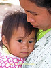 Lao Loum Child  in the Comfort of her Mother's Aems- Tahsang Village, Isaan Region Thailand