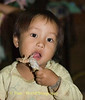 Hmong Child Tearing Into a Piece of Chicken at Birthday Party