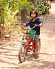 Mai Rides Her Bicycle Through Tahsang Village On A Hot Day