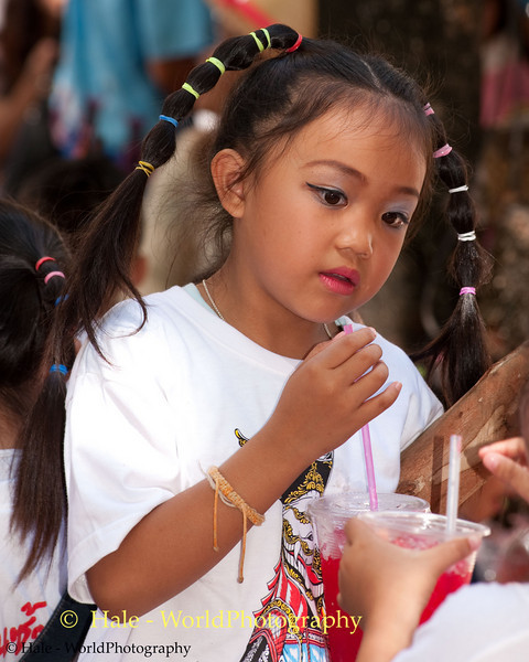A Young Lao Loum School Girl Enjoys Her Drink After Dancing